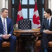 Justin Trudeau et Andrew Scheeer, assis, se regardent.