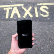 Un téléphone intelligent affichant l'application Uber, au-dessus d'une chaussée sur laquelle il est écrit : « TAXIS ».