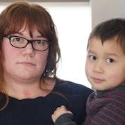 Une femme qui tient un enfant dans ses bras.