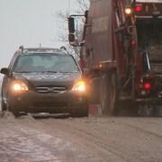 Une voiture et un camion à ordures circulent sur une route de Québec durant un épisode de pluie verglaçante.
