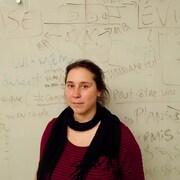 L'organisatrice communautaire au Comité logement du Plateau, Vicky Langevin. Elle pose devant un tableau rempli de notes.