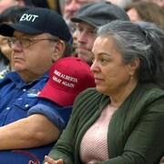 Des personnes assises avec des casquettes Make Alberta Great Again et Wexit dans une école de Calgary pendant un rassemblement du mouvement Wexit.