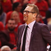 L'entraîneur Nick Nurse sourit en regardant au ciel pendant un match des Raptors.