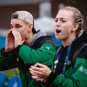 Deux athlètes encouragent leurs coéquipiers.