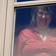 Une femme derrière une fenêtre.