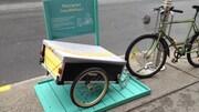 Une roulotte à vélo, à deux roues, est attaché à un poteau sur un raque vert à côté d'une bicyclette.