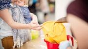 Une femme avec un bébé dans les mains tient un sac pendant qu'il se fait remplir de grains.
