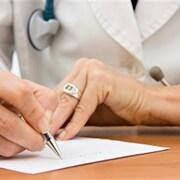 Plan serré des deux mains d'une personne en sarrau écrivant une ordonnance.
