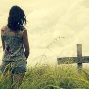 Une femme se recueille devant la tombe d'un ami.