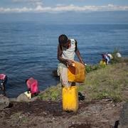 Une femme remplit son bidon d'eau au lac Kivu, en République démocratique du Congo.