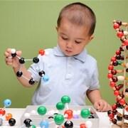 Un garçon s'amuse avec des représentations d'atomes
