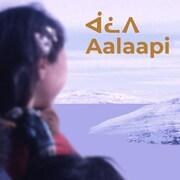 Photo de deux Inuits sur fond de paysage enneigé avec l'inscription Aalaapi en inuktitut.