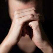 Une femme dont le visage est caché par ses mains en premier plan, paume droite sur poing gauche.