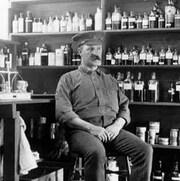 Un soldat assis dans une pièce remplie de bouteilles d'alcool.