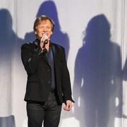 André-Philippe Gagnon vêtu de noir sur scène, en arrière-plan des silhouettes de six personnes en ombres chinoises sur un rideau blanc.