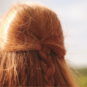 Couverture du livre <em>Anne... La maison aux pignons verts</em>, de Lucy Maud Montgomery, réédition 2001. On y voit la chevelure rousse tressée d'Anne, photographiée de dos.