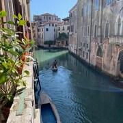 Une gondole sur l'eau entre deux rangées de maisons.