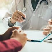 Les bras d'un médecin et de sa patiente discutant, assis à un bureau.