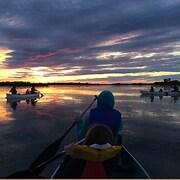 Des enfants et des adultes dans trois canots sur un lac, au soleil couchant