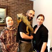 un homme, une femme et une jeune-fille entourent un reptile exotique.