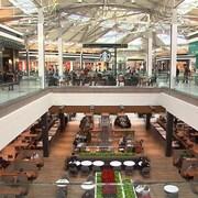 Des gens circulent dans un centre commercial à deux étages. Au bas, on voit une série de tables et des arrangements floraux, tandis qu'en haut, un café Starbucks trône au centre des différentes boutiques.