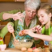Une grand-mère avec deux petites filles cuisine ensemble