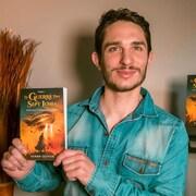 Kenan Olivier tient son roman dans ses mains.