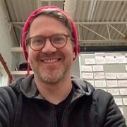 Dominic Desjardins, scénariste et réalisateur chez Zazie Films portant un bonnet rouge devant un tableau couvert de post-it