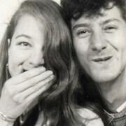 Une femme et un homme regardent la caméra. La femme cache sa bouche avec sa main, l'homme sourit.