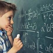 Un enfant devant un problème mathématique sur un grand tableau noir.