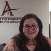 Une femme qui porte des lunettes et derrière elle un mur où est écrit : Alliance des femmes de la francophonie canadienne.