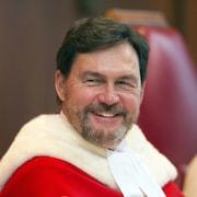 Un homme dans une toge de juge sourit en regardant de côté.