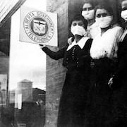 Quatre jeunes femmes portant des masques devant un édifice. Photo noir et blanc d'époque.