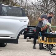 Un homme s'apprêtre à remplir une voiture de nourriture.