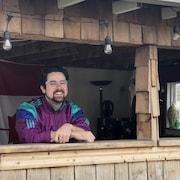 Un homme se tient derrière un comptoir à l'extérieur.