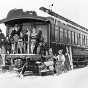 Des élèves et un enseignant sur le pont du wagon avec des raquettes dans les mains.