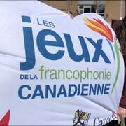 Une jeune fille tient le drapeau des jeux gonflé par le vent.