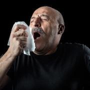 Un homme éternue dans un mouchoir.