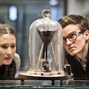 Deux étudiants regardent l'entonnoir contenant la poix sous une cloche de verre.