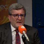 Un homme en costume sombre, à chemise blanche et à cravate aux motifs roses parle au micro.