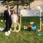 Marcel et Célia Roussel posent autour de coeurs avec l'inscription 50 pour souligner leur 50e anniversaire de mariage