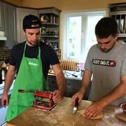 Deux jeunes hommes travaillent dans une cuisine.
