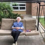 Marthe Dallaire âgée de 91 ans, est assise confortablement dans une balançoire à l'extérieur du Foyer des pionniers de Hearst, où elle continue de faire du bénévolat à chaque semaine.