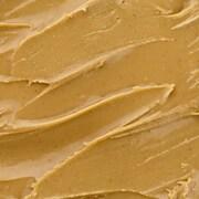 Du beurre d'arachide est tartiné sur une tranche de pain.