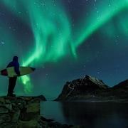 Un homme se tient au bord de l'eau, un surf sous le bras, et admire les aurores boréales vertes au-dessus de montagnes enneigées.
