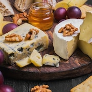 Un plateau de fromages avec des craquelins, des raisins, des noix et du miel.