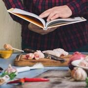Un homme tient un livre de recettes au-dessus d'un comptoir de cuisine plein d'ingrédients.