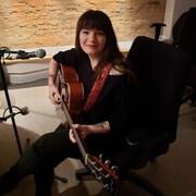 Geneviève Racette, autrice-compositrice-interprète montréalaise, placée assise sur une chaise de bureau, guitare à la main et devant son micro