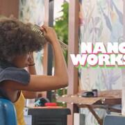 Image promotionnelle dans laquelle on voit une jeune femme travailler ses cheveux frisés serrés dans au miroir d'un salon de coiffure