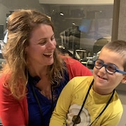 Une femme et un enfants dans un studio radio de Radio-Canada